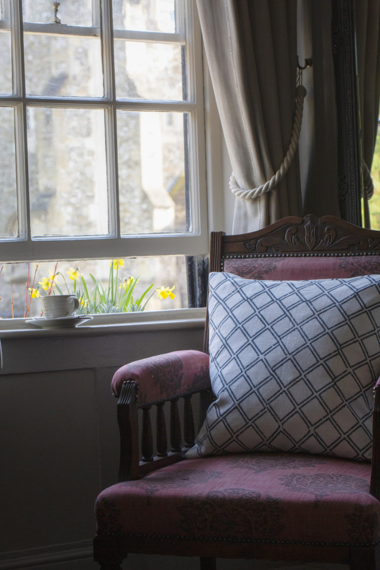 old fashioned arm chair next to window